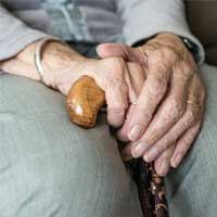 Elderly person sitting with walking stick