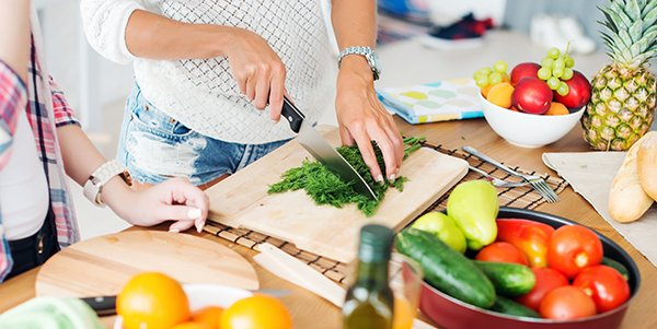 Woman chopping up herbs with fresh fruit and vegetables around her