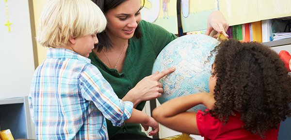 Teacher showing two young children a globe