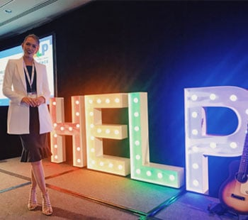 Anja Christoffersen standing in front of a help sign